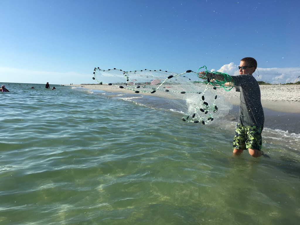 A student practices throwing a cast net during a fishing lesson at Sanibel Sea School.
