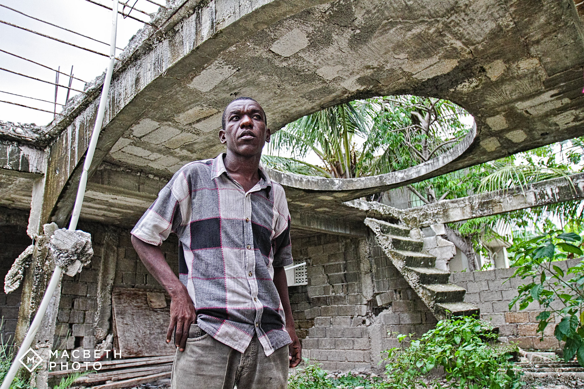 John Robert, earthquake survivor and REBUILD globally Supervisor and Designer. He is standing in what used to be his home prior to the earthquake.