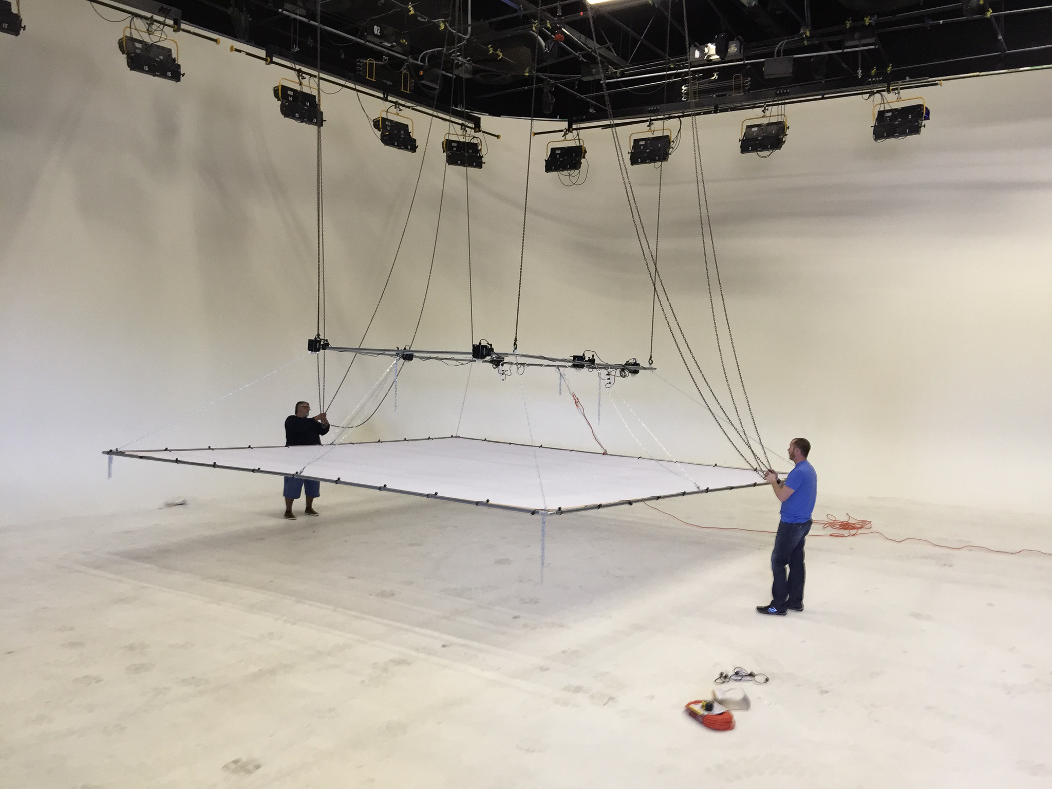 We have liftoff! 20' x 20' silk panel installed using 48 ball-bungees. Raising the rig requires four separate chains to be pulled simultaneously.