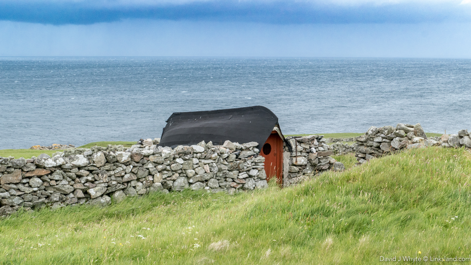 It looks like a Hobbit's Croft - a useful way to use an old boat...