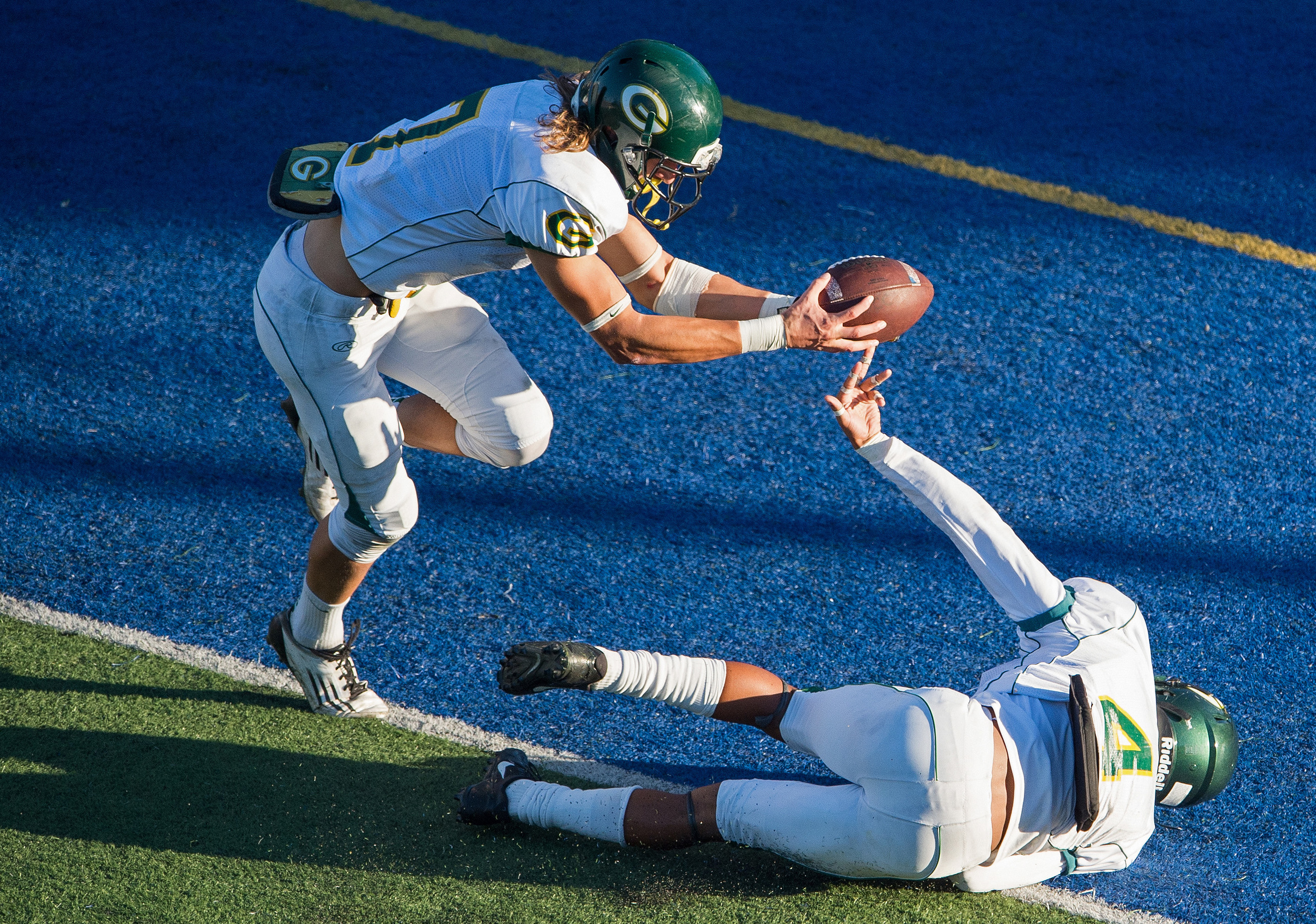 Grossmont Griffins wide receiver Christopher Lachance (7) and defensive back Brandon Payne (4) are unable to keep a punt out of the end zone during the second half of a game against the Santa Ana Dons at Santa Ana Stadium.