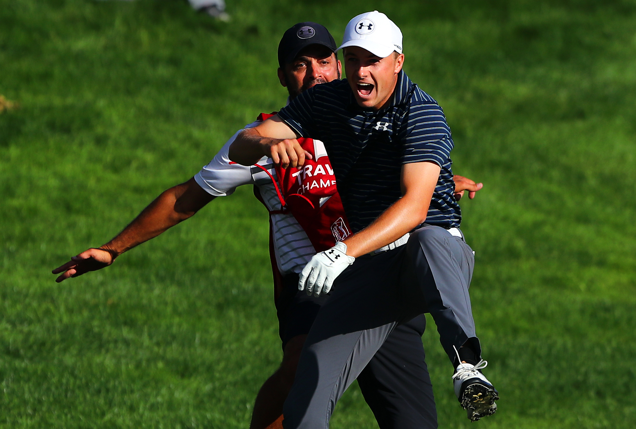 CROMWELL, CT - JUNE 25: Jordan Spieth of the United States celebrates with caddie Michael Greller after chipping in for birdie from a bunker on the 18th green to win the Travelers Championship in a playoff against Daniel Berger of the United States (not pictured) at TPC River Highlands on June 25, 2017 in Cromwell, Connecticut. (Photo by Tim Bradbury/Getty Images)