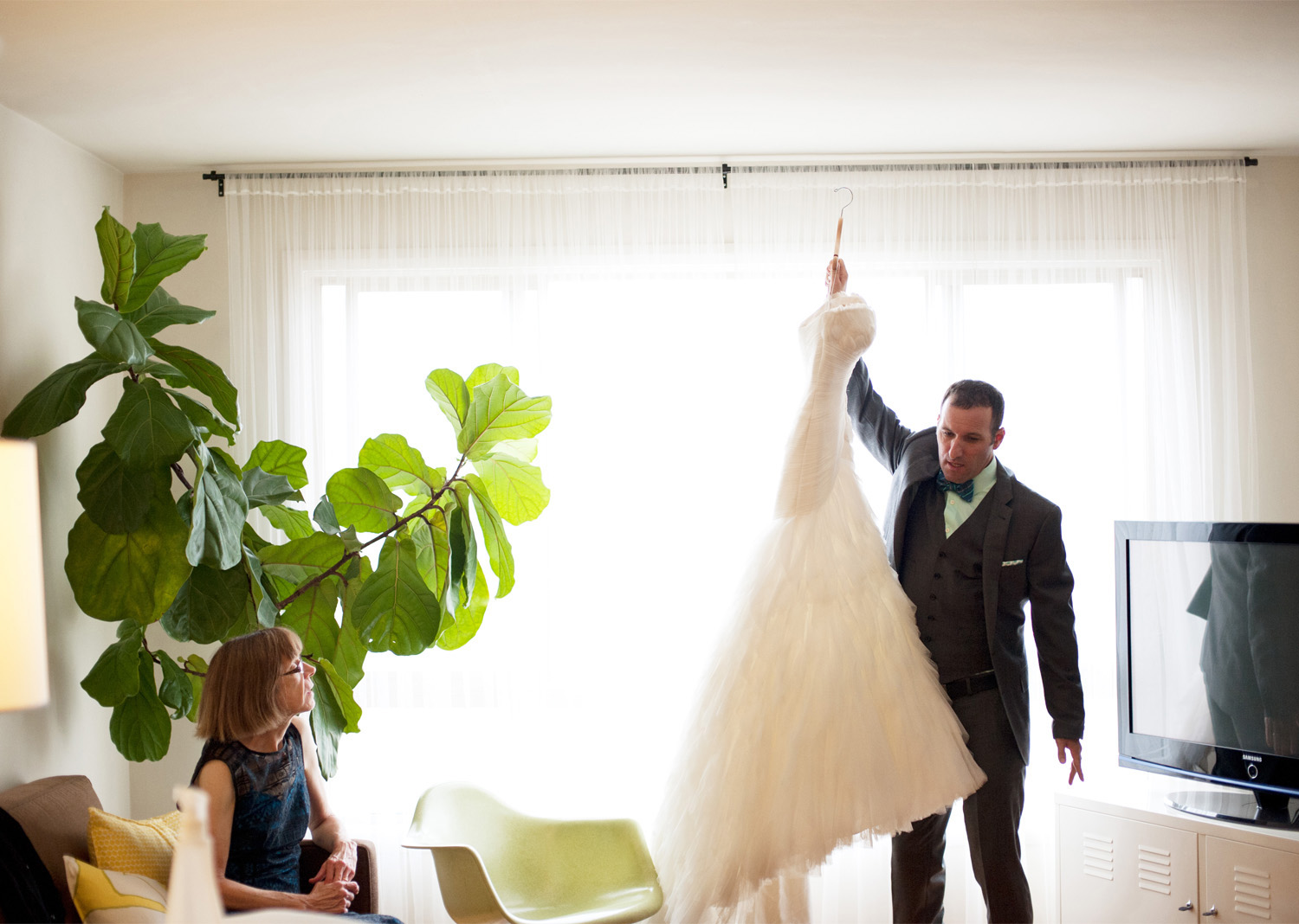 groom helps bride get ready by carrying her dress to her
