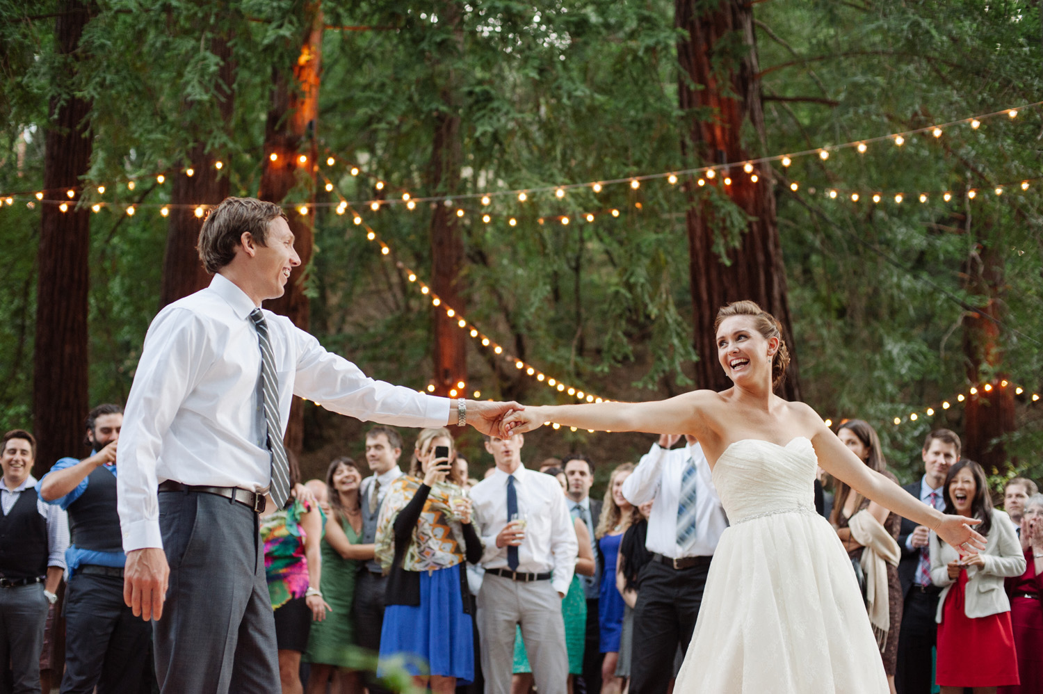 bride and groom first dance in a redwood forest with twinkle lights as guests watch joyfully