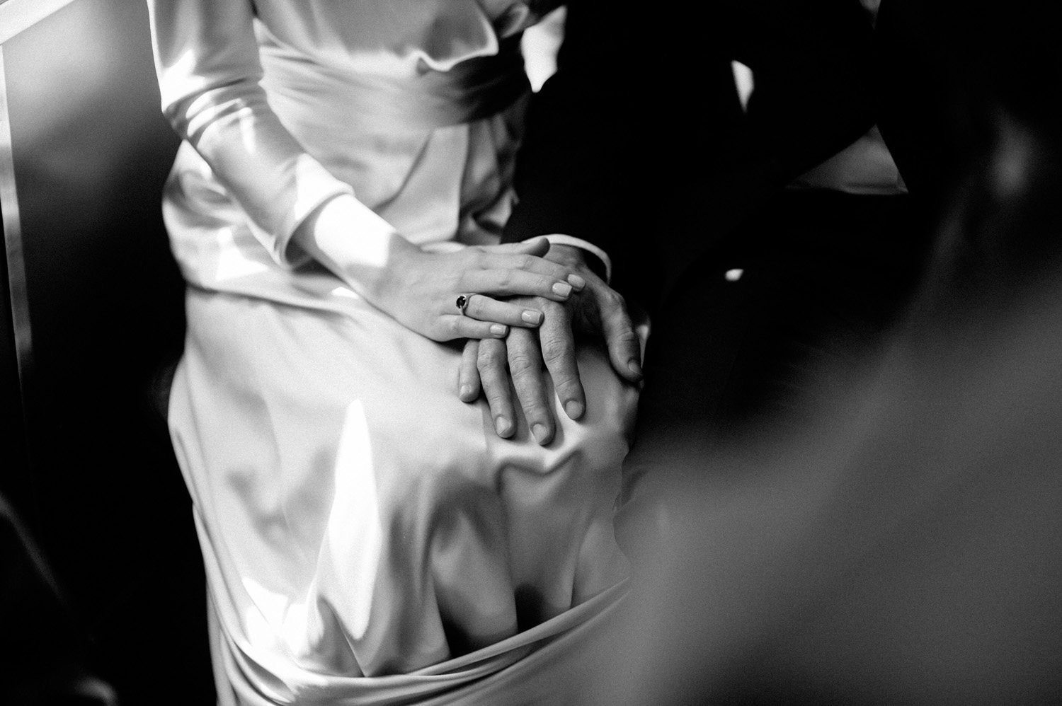 bride and groom tenderly touch hands in a wedding day detail photograph in black and white