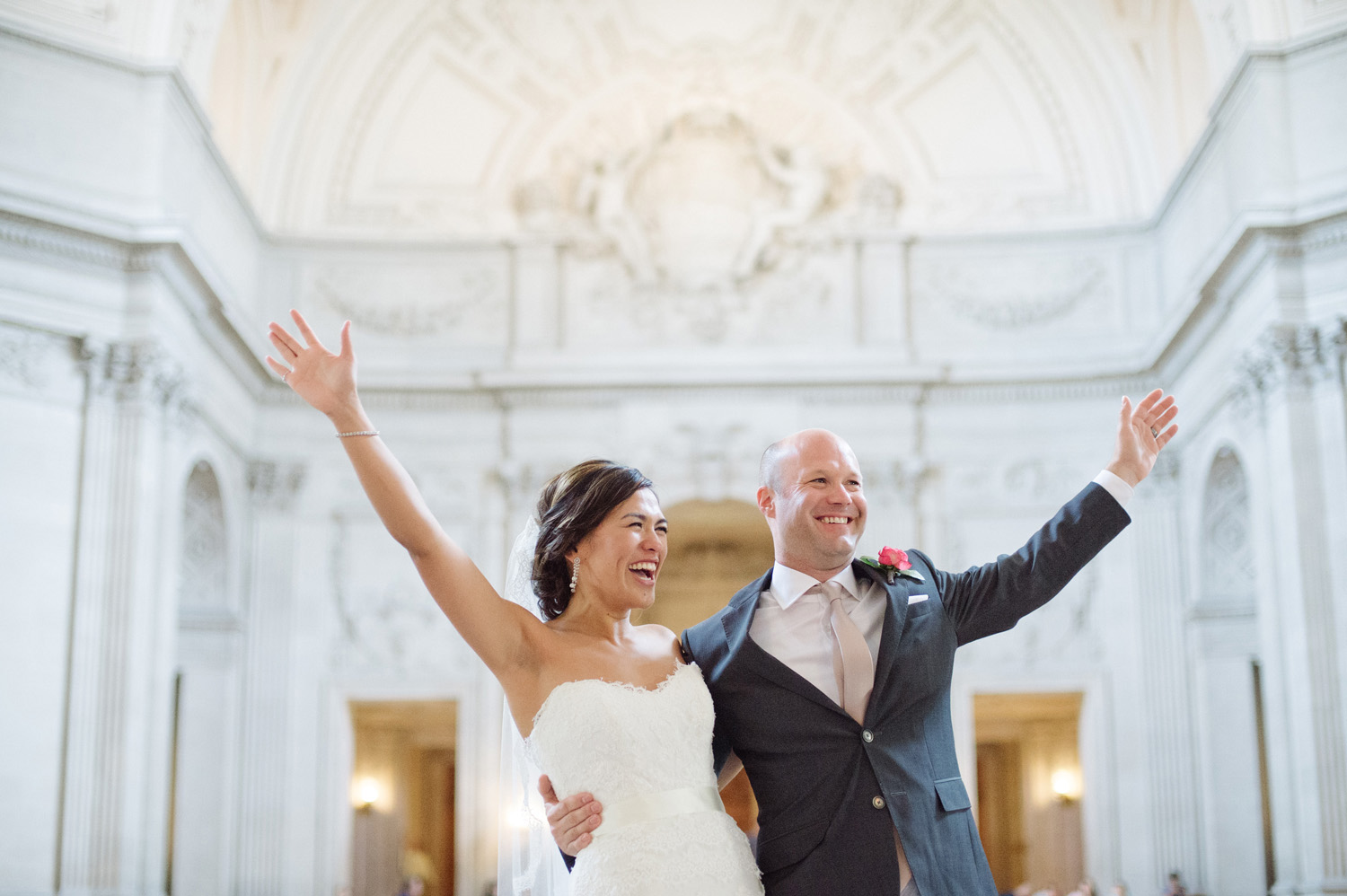 bride and groom hold each other in a celebratory embrace after they get married in San Francisco City Hall