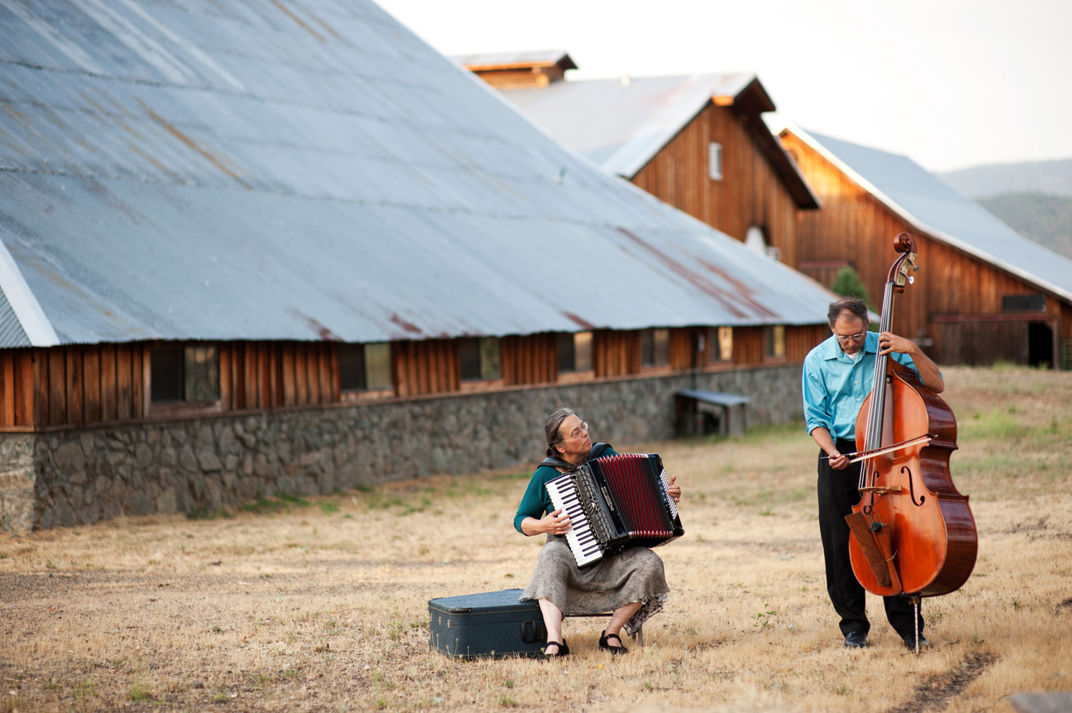 klezmer wedding ceremony musicians sitting in a field in front of a barn in rustic setting