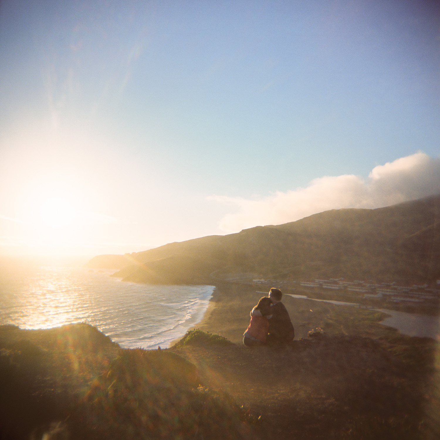 couple watches the sunset over the Rodeo Lagoon in Marin