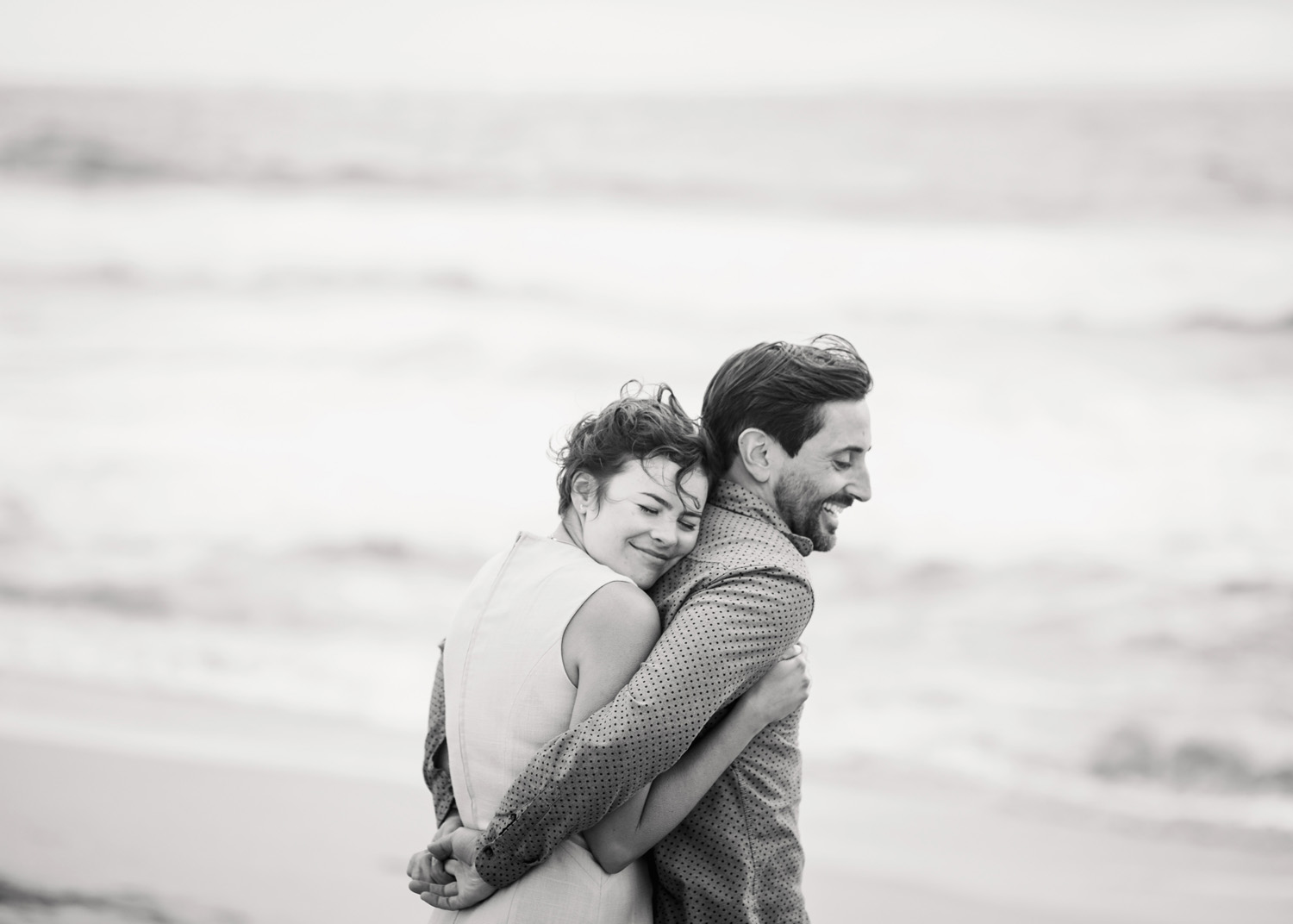 beach engagement photo couple hugs to keep warm on a foggy windy day in at the beach
