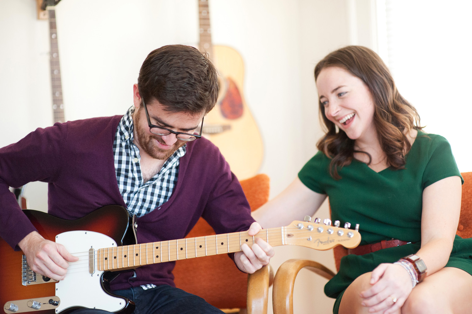 engagement session at home couple plays music and laughs