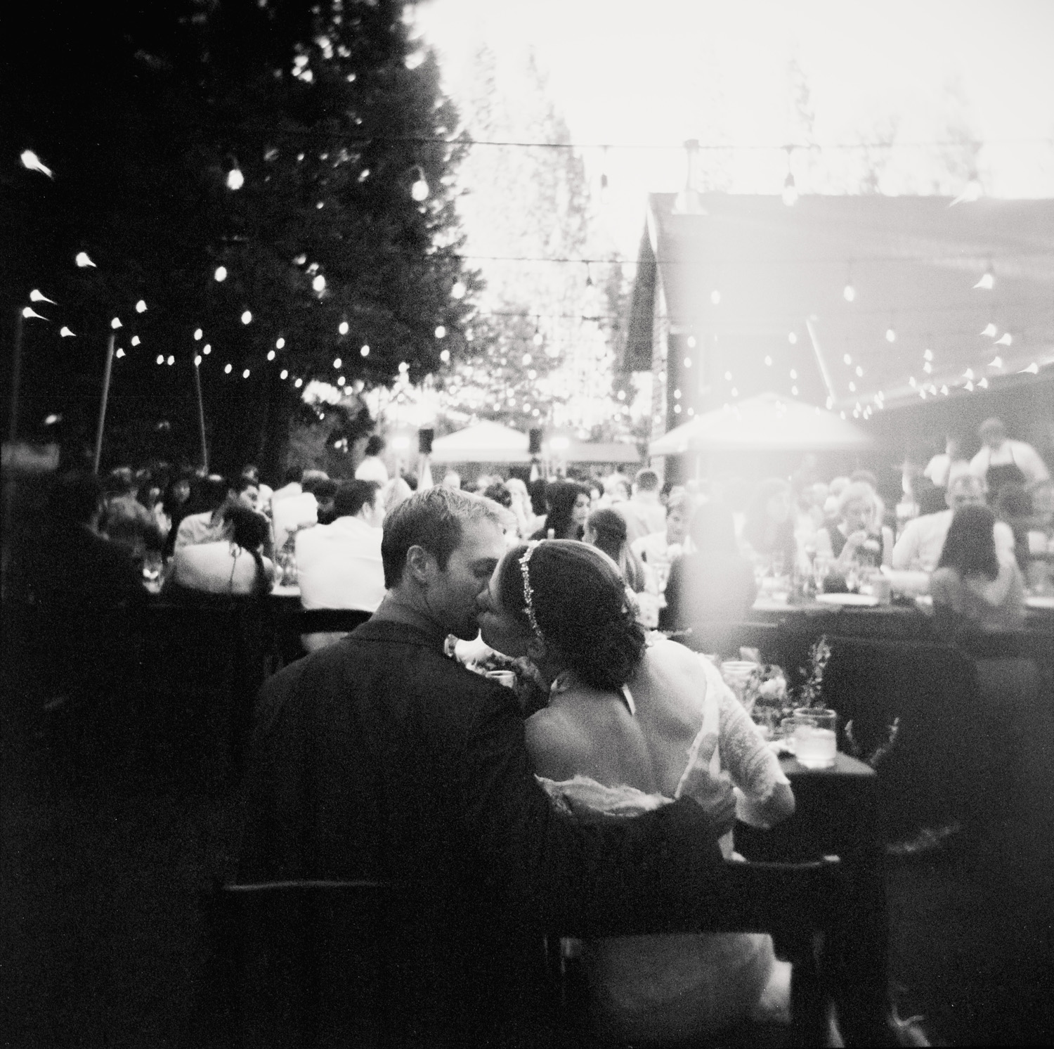 bride and groom share a kiss seated at the sweetheart table during their outdoor wedding reception in Anderson Valley, CA