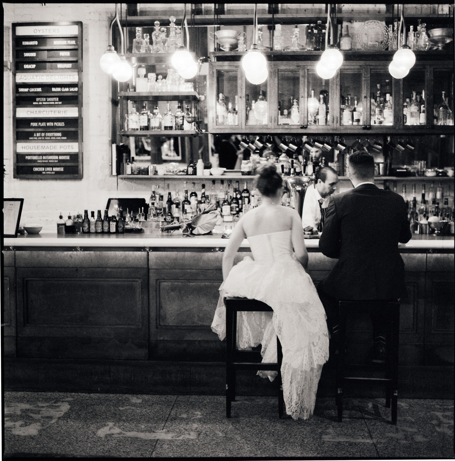 Bride and groom sit alone at the bar at Saxon and Parole in New York City black and white film photograph