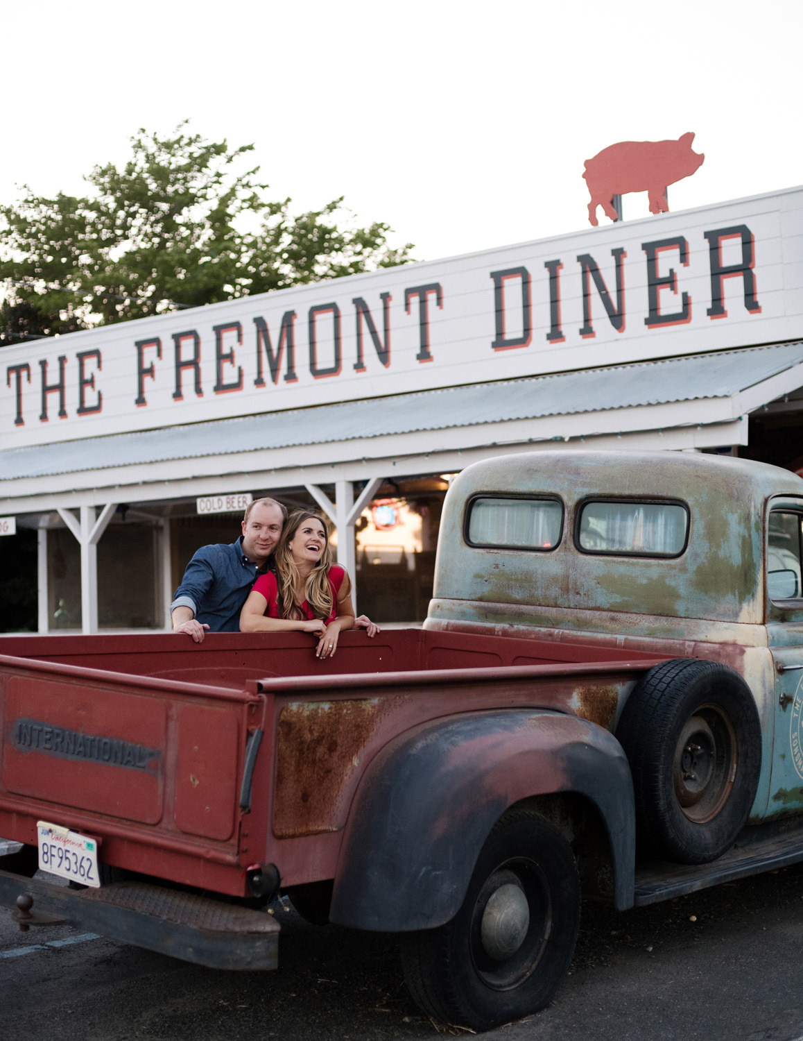 engagement photo at the Fremont Diner in California couple leans on vintage truck