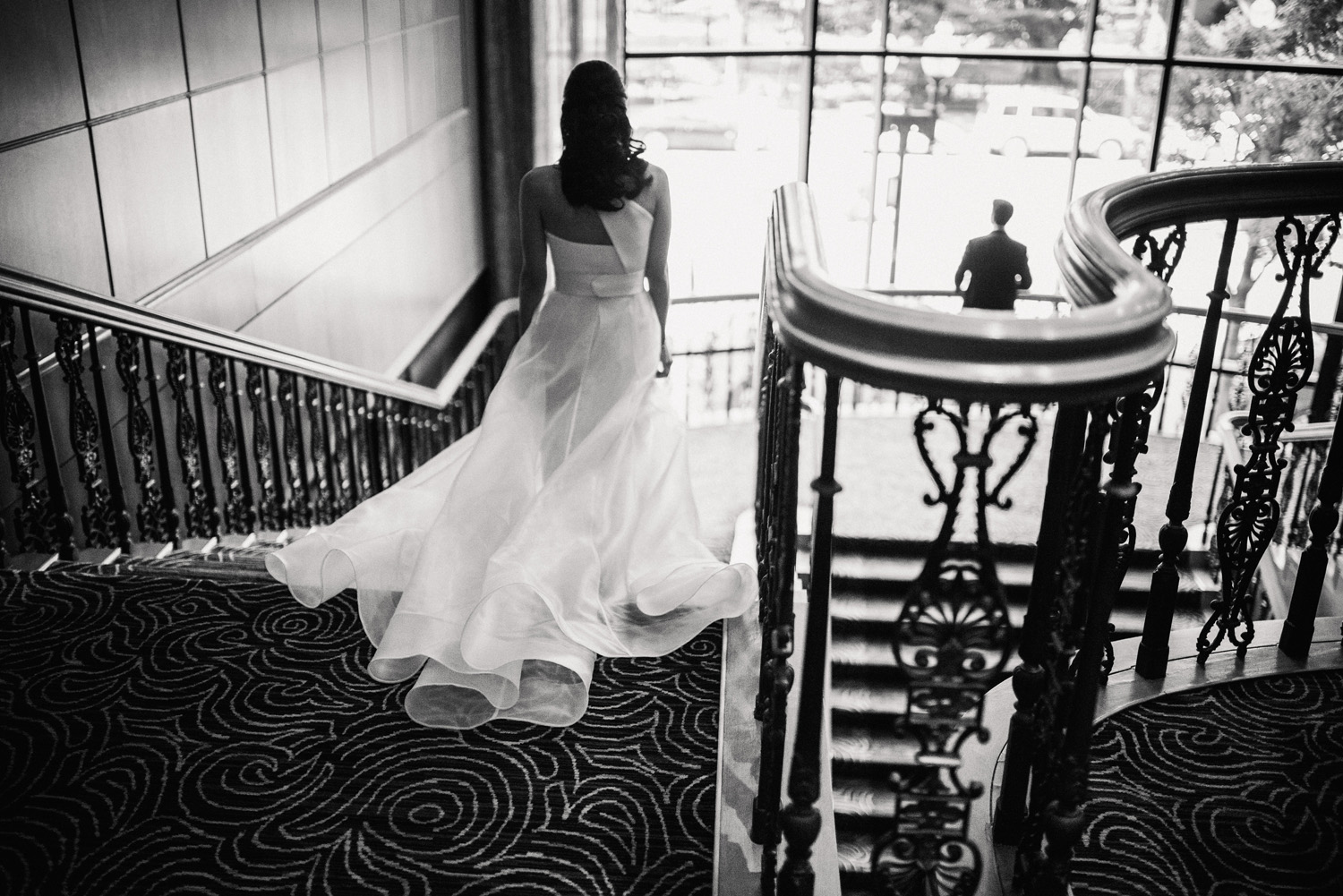 Bride walks down the grand staircase at the Boston Four Seasons for her first look before her modern, urban wedding ceremony