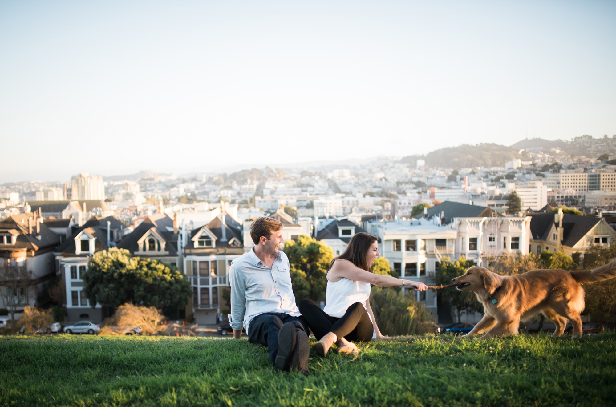 San Francisco engagement photo with couple sitting on the hill playing fetch with a dog