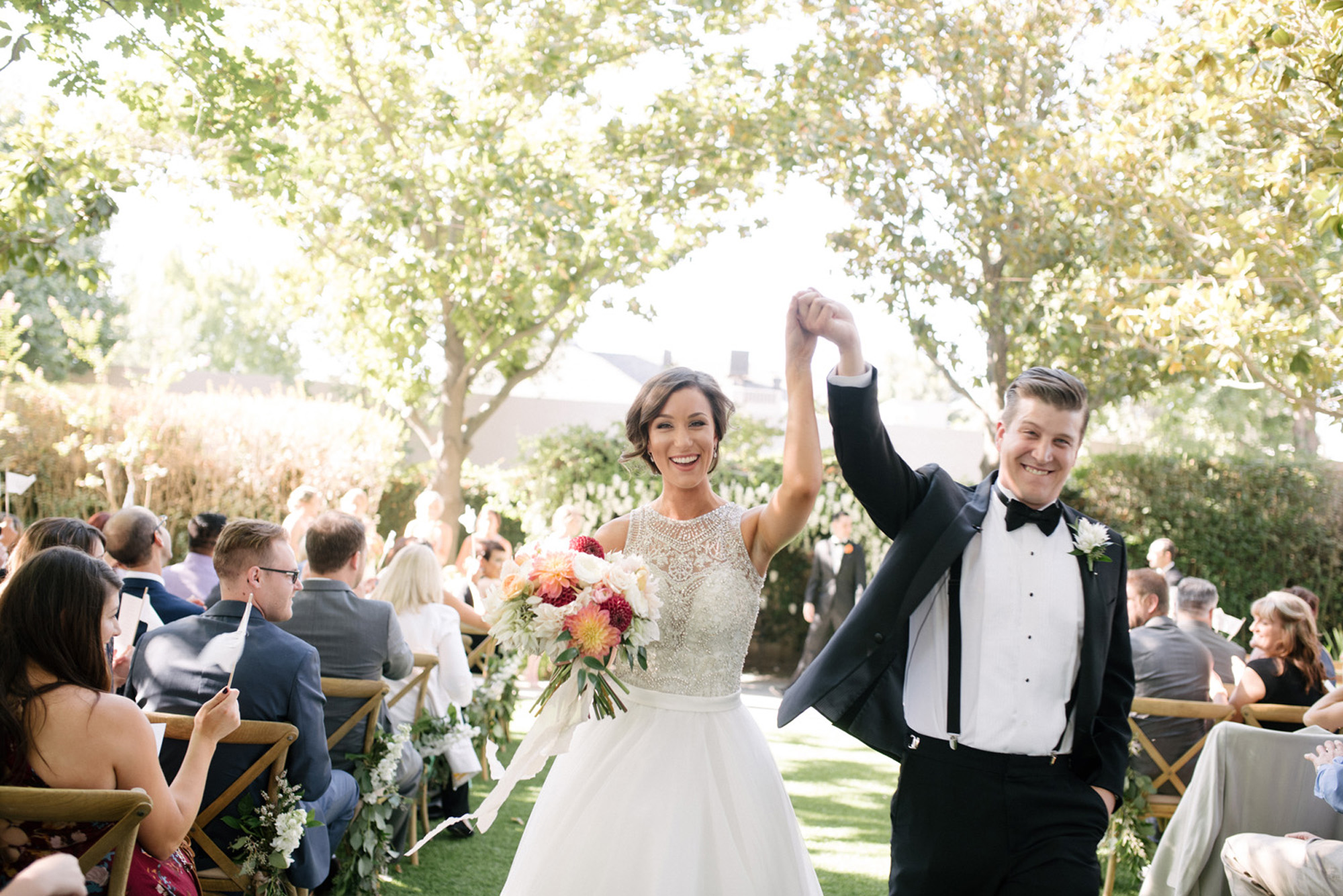 classic bride and groom exit their wedding ceremony with hands held high with joy documentary
