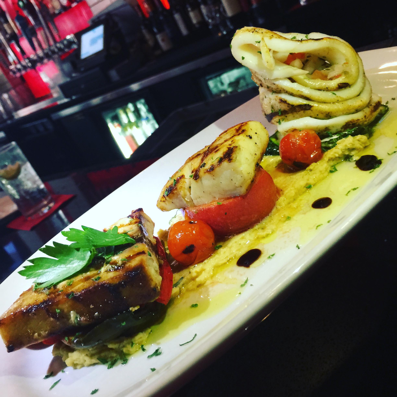 Grilled fish sampler mahi mahi, calamari, swordfish with hummus and grilled vegetables