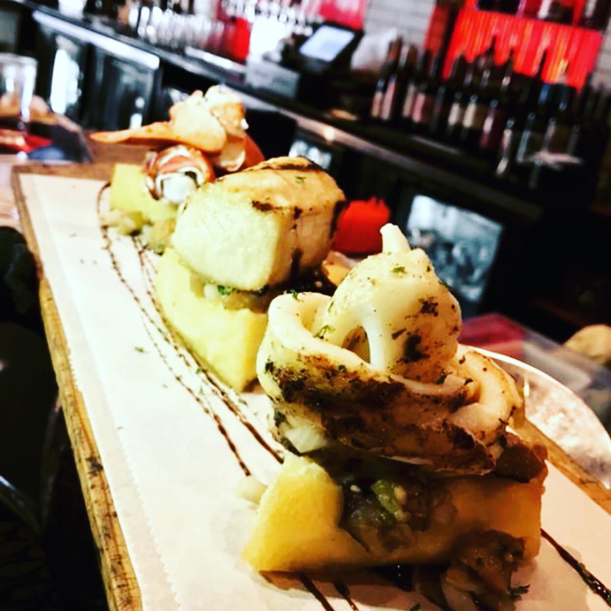 Fish bite: grilled lobster, calamari and mahi over fried truffled polenta and caponata
