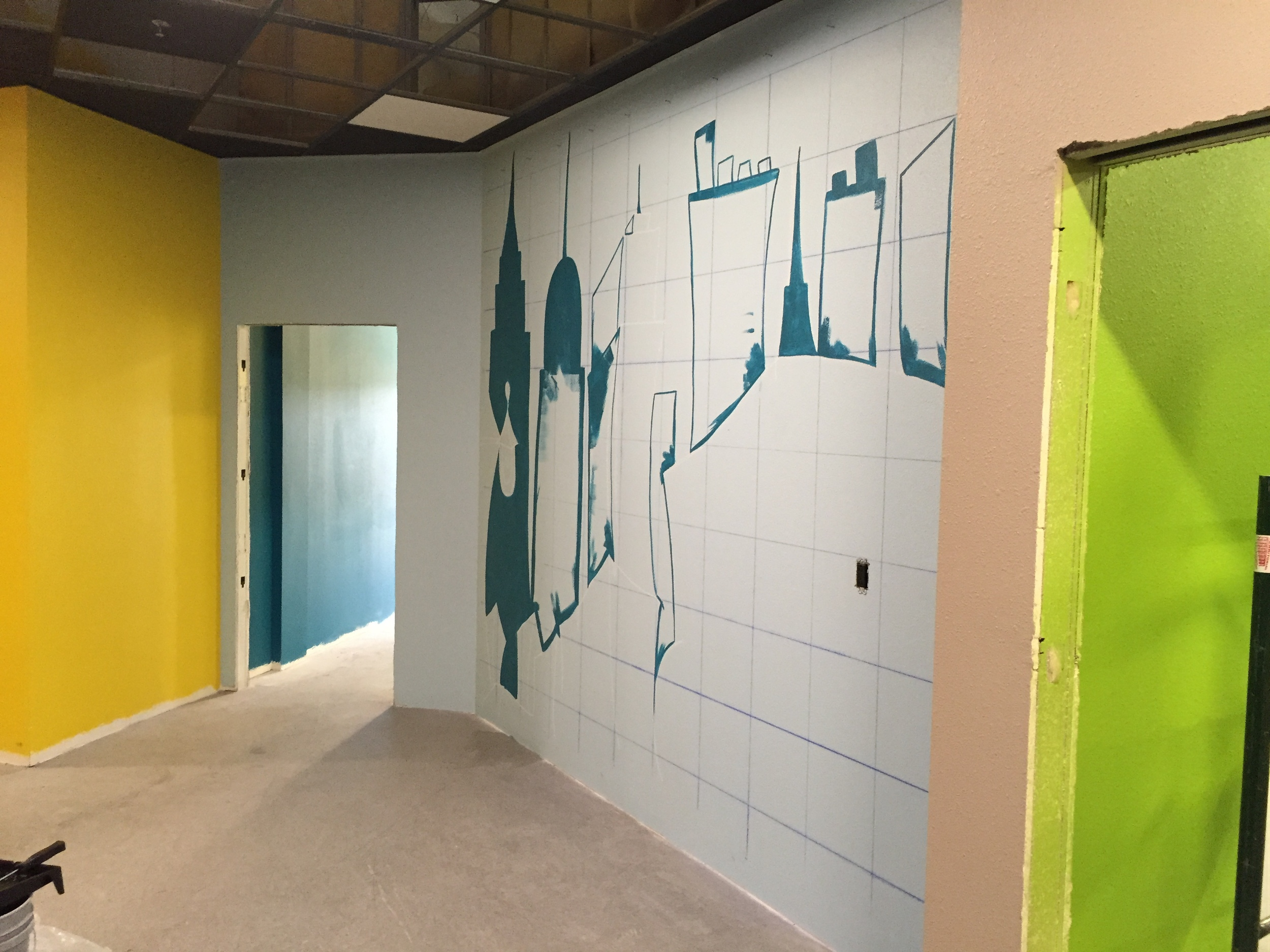 The beginnings of the mural in the Kids' City check-in area.