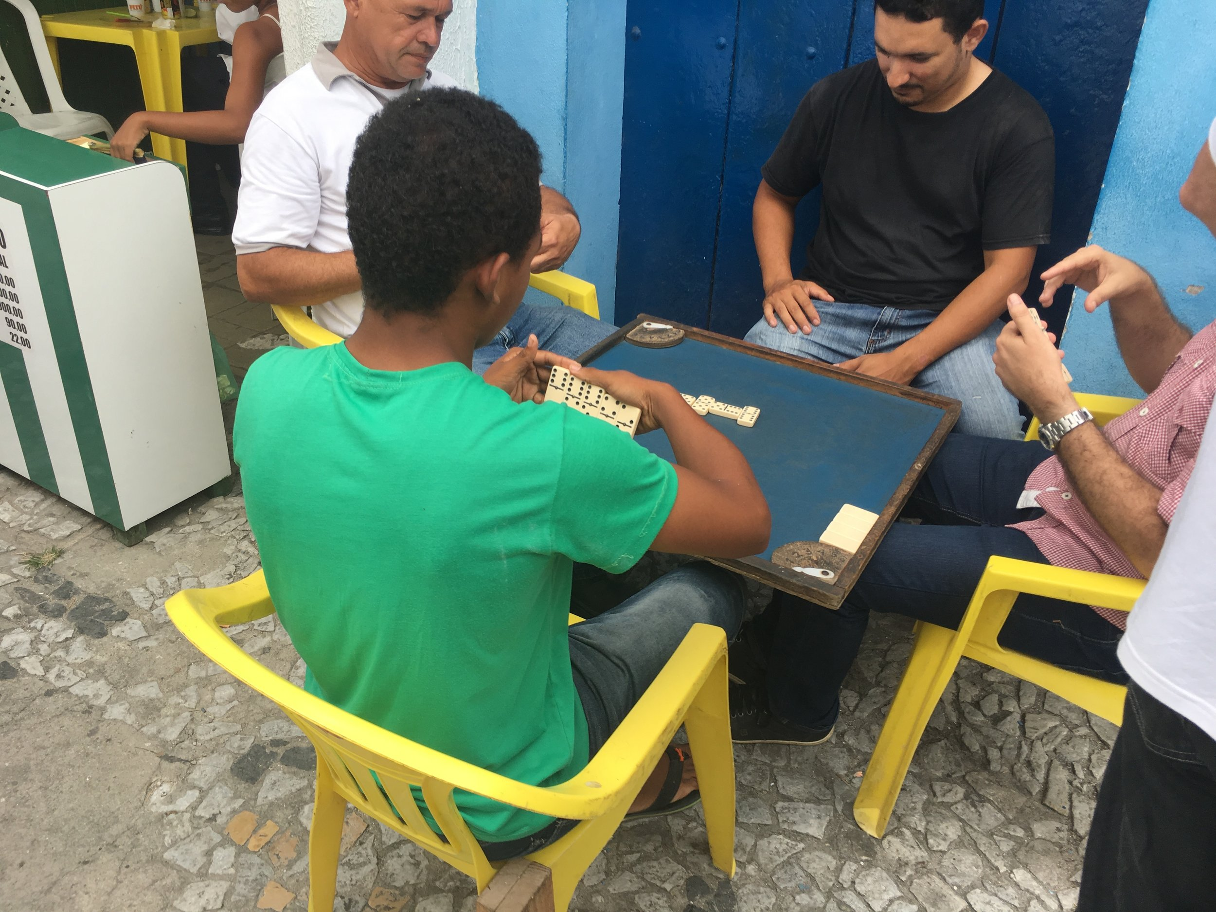 Locals play a game of dominos.