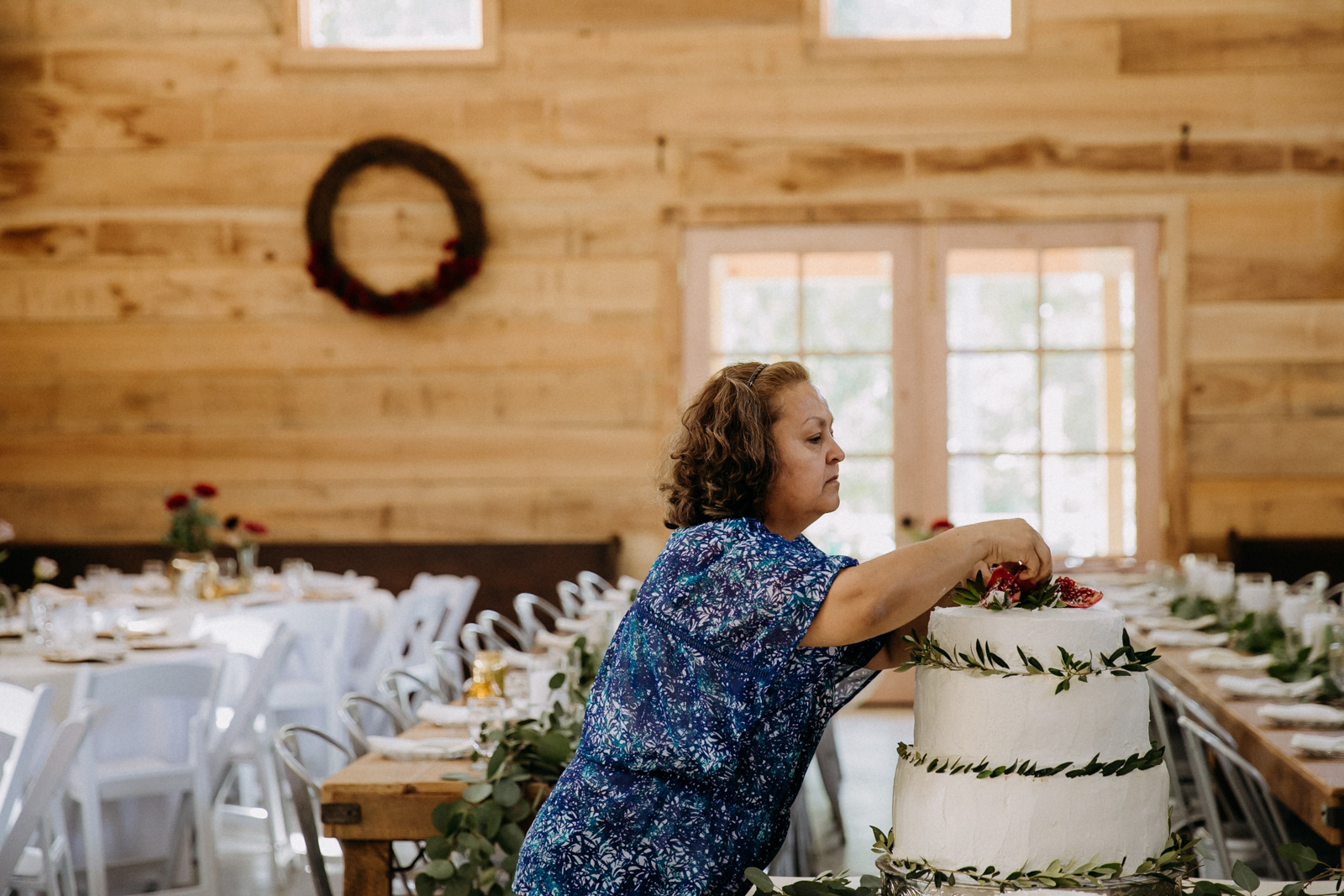 Mother-of-the-groom decorating the cake with olive leaves