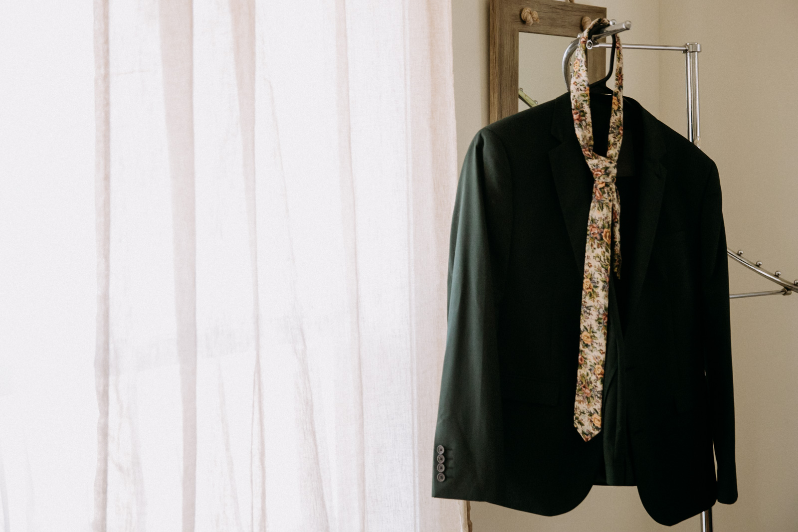 Groom's forest green suit and floral tie