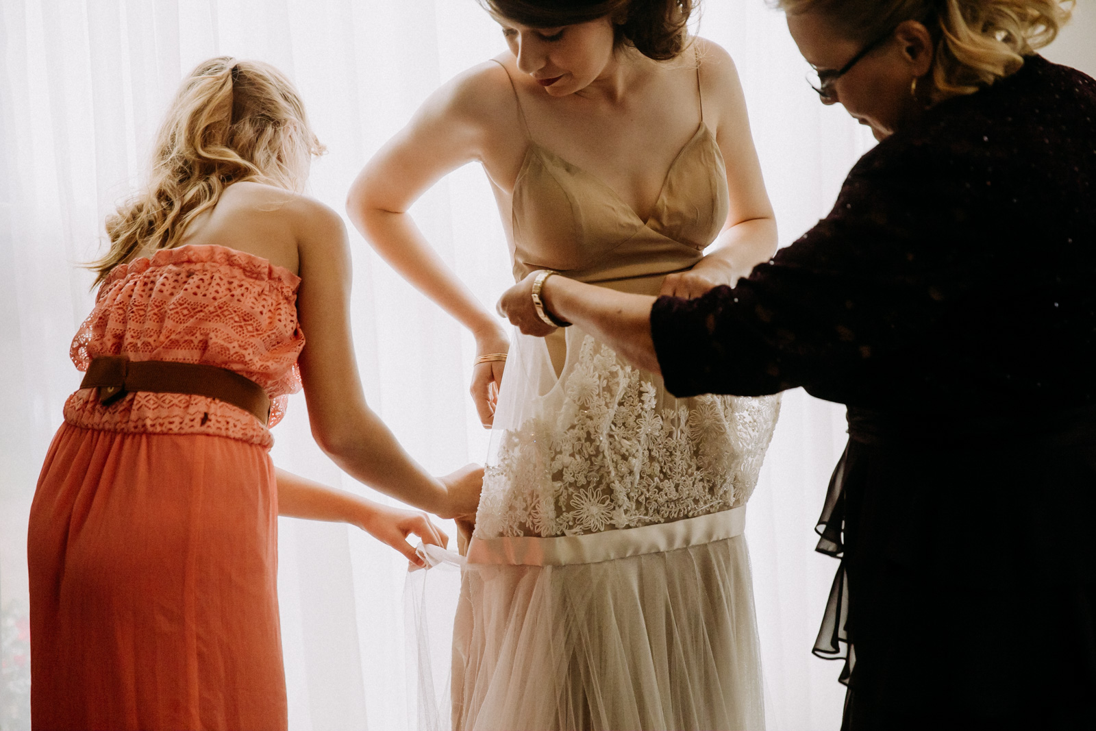 Bridesmaids and mother-of-the-bride helping the bride get dressed
