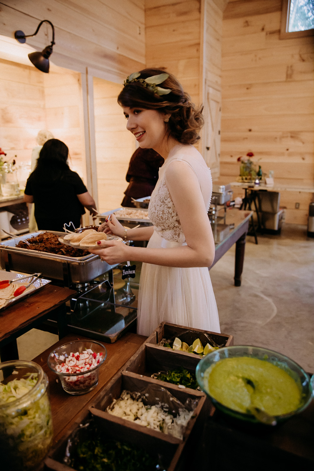 The bride getting food from the taco bar