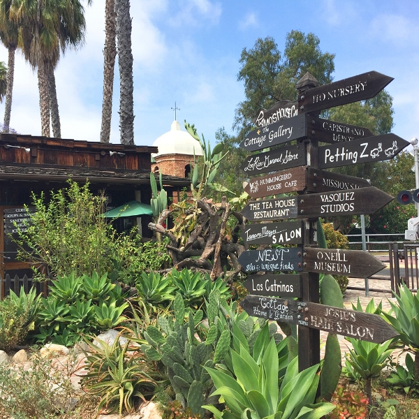 Wooden signs in San Juan Capistrano's Los Rios District with the train depot in the background.