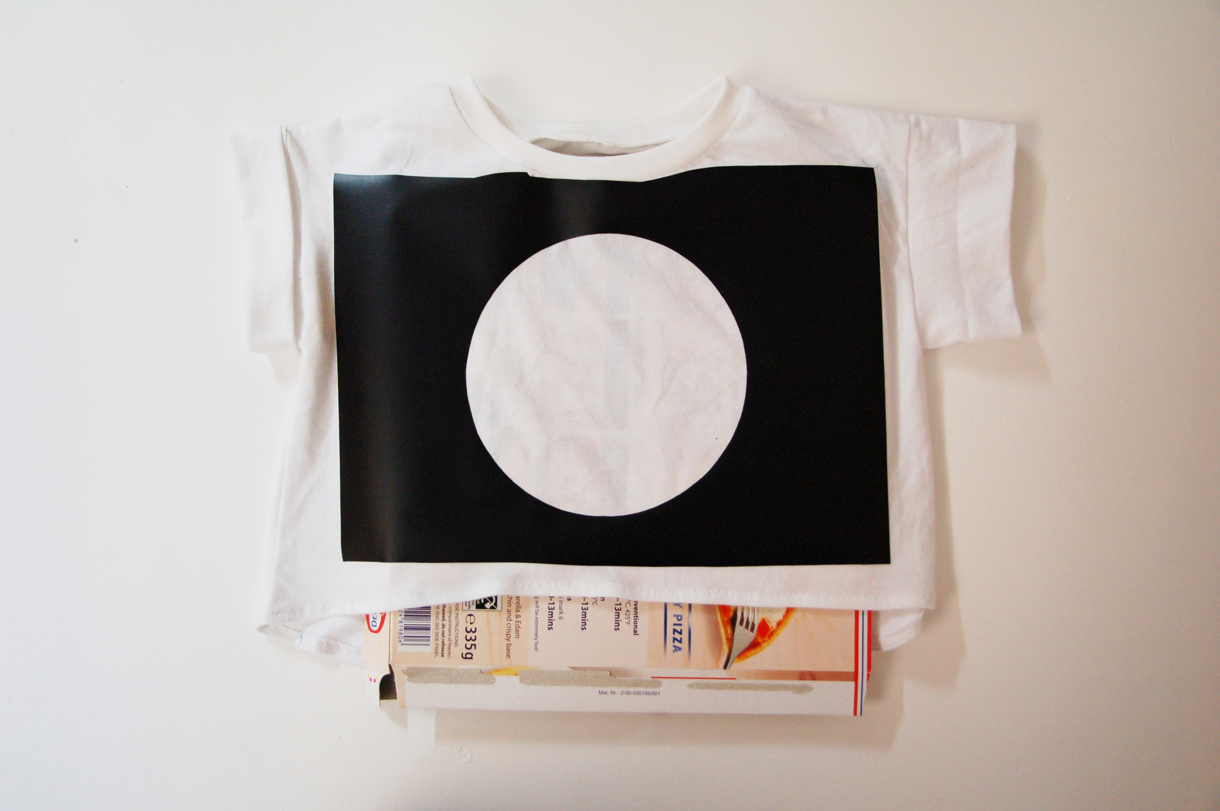 Insert a piece of scrap card inside the t shirt to prevent the paint going all the way through to the back.