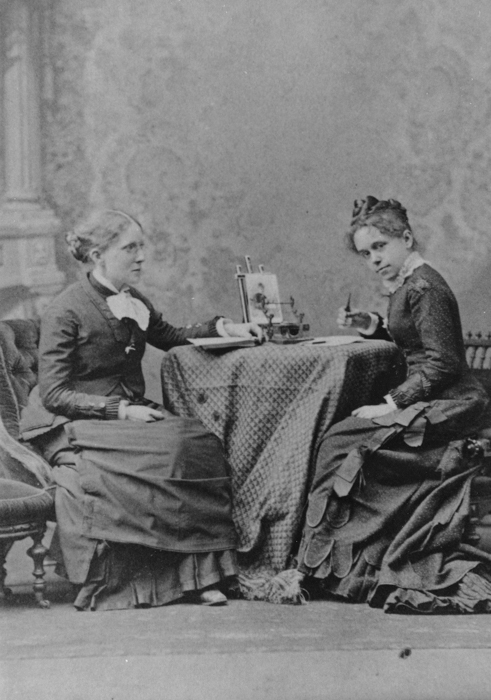 Historic Image of Frances Willard and her assistant Anna Gordon   The Willard house, built by Willard's father and continually occupied by the WCTU, has been mostly restored and captures a sense of what life might have been like within it's walls when Willard resided there, all abustle with fervent women researching, writing, planning and distributing information. Unusually, there are a number of photographs of the interior of the house in its heyday capturing life in action, so the translation from organizing hub to house museum and back again was not so difficult to imagine. The rooms are small and the light limited which pushed my creativity and technical skills as a photographer. After making initial survey images of the house I went home and examined the images, meditated on them, and conjured my own version of the activities that might have gone on within this hive and how they relate to present day organizing. I then mapped out what I envisioned for each room of the house, making costumes and props and calling on friends to become actors in vignettes. At each shoot I told a story of the characters in the vignette and the particulars of what they were doing and why. I asked each woman to imagine that they were existing as a woman of the past, present and future, a bridge anchored in history. Although they wore the clothing of the past, they bore the wisdom and insight of today.