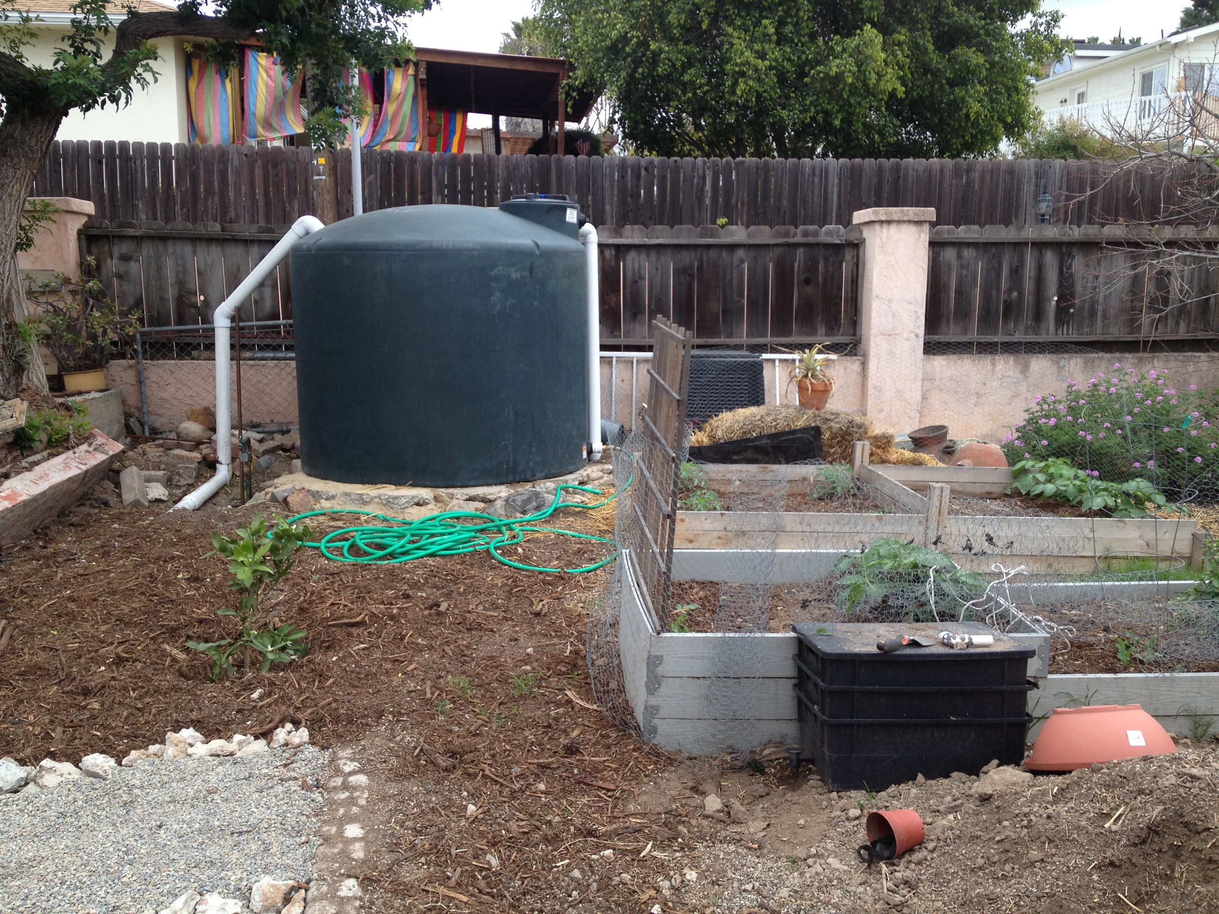 This tank collects rainwater from pipes that drain from the roof, go underground and come back up into the tank, without a pump.  That doesn't necessarily seem intuitive, but it works!