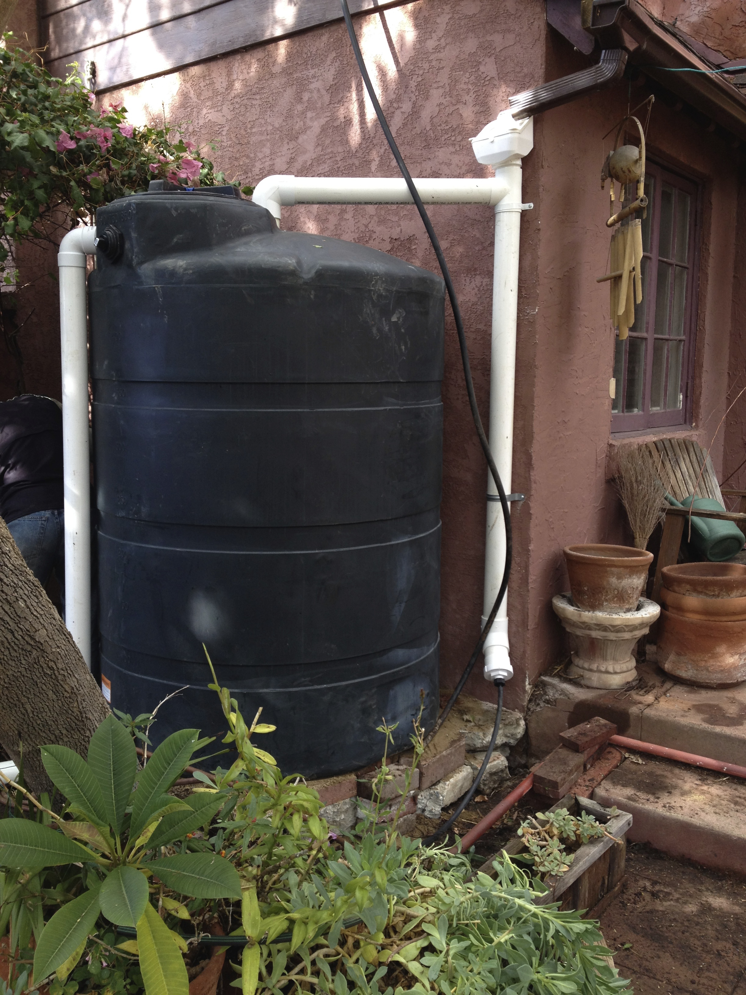The sloped screen box under the rainwater downspout is called a Leaf Filter. It diverts leaves and other large debris from your tank. The standpipe directly under the leaf filter is a homemade First Flush Diverter. The first amount of rain that washes any small debris including bird poop, dust, pollen, etc will collect in this standpipe. As the water continues to wash off the roof, the water has less pollutants in it and overflows to fill the tank. The first flush diverter can then be easily drained, and opened up to be cleaned.