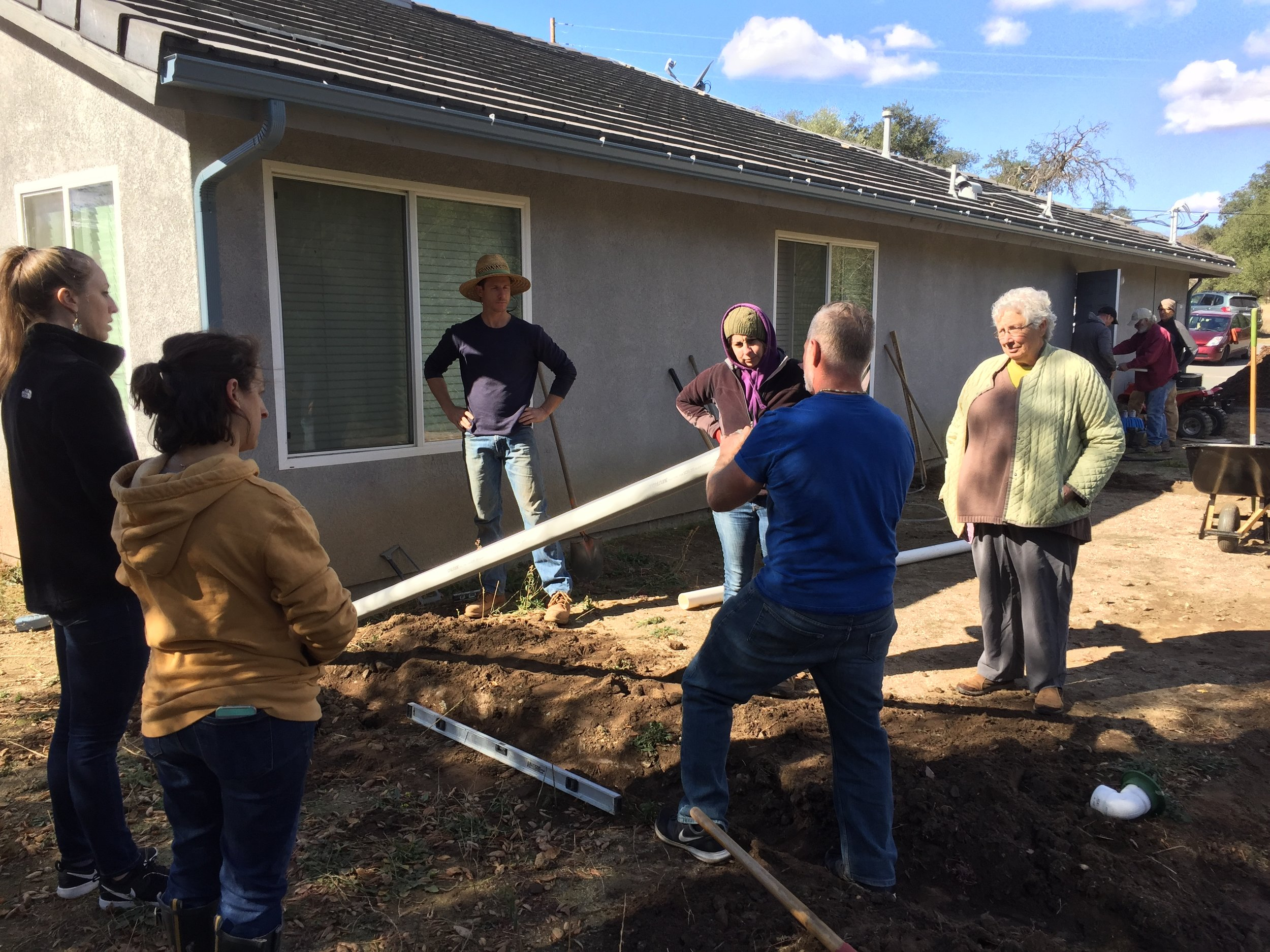 Working together to reroute rainwater downspout into laundry greywater basin