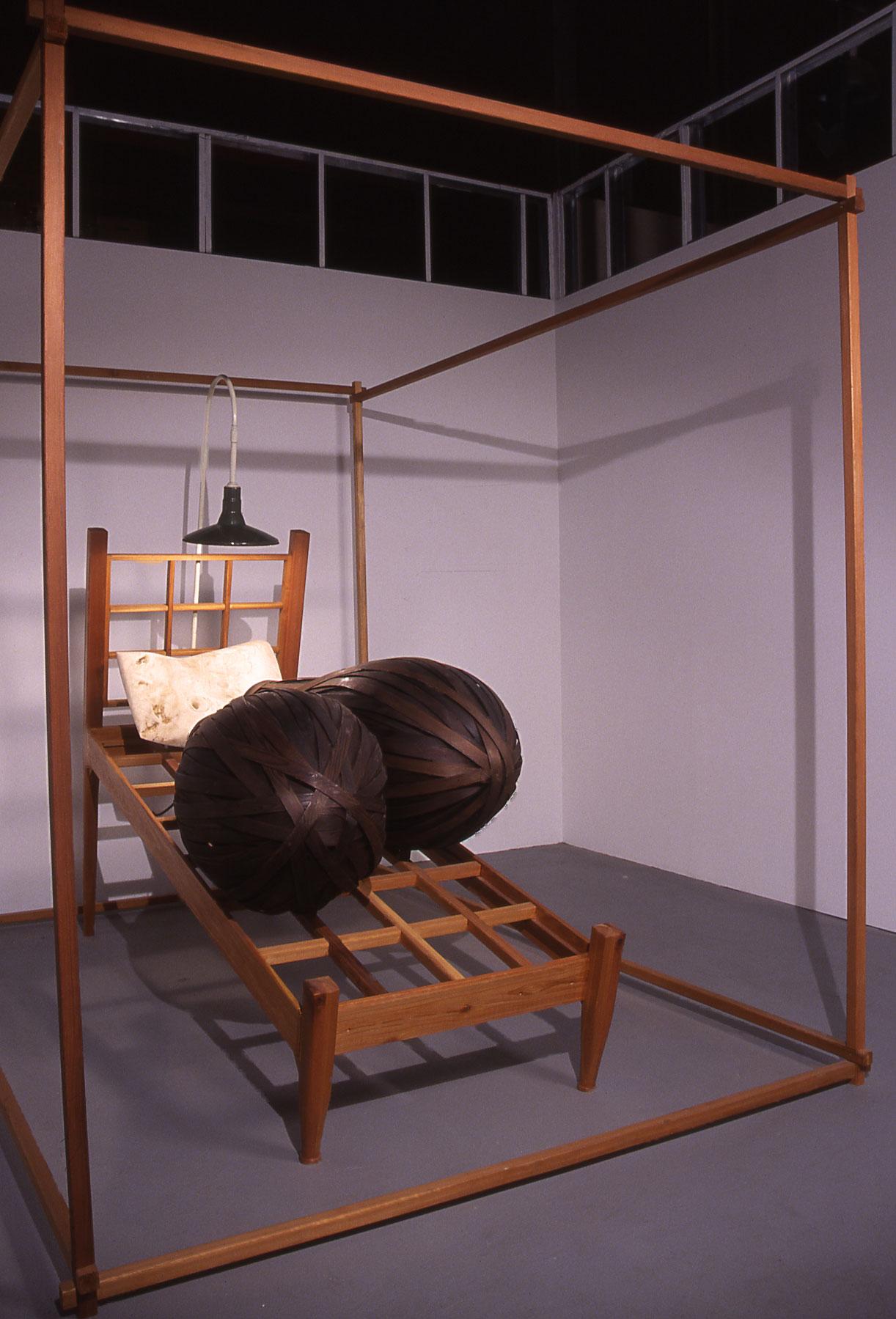 """Sleeping Double in a Single Bed"", wood sculpture 8' h x 7' w x 8' d ; ebonized Cedar, carved Poplar, electric light; © Tom Gormally"