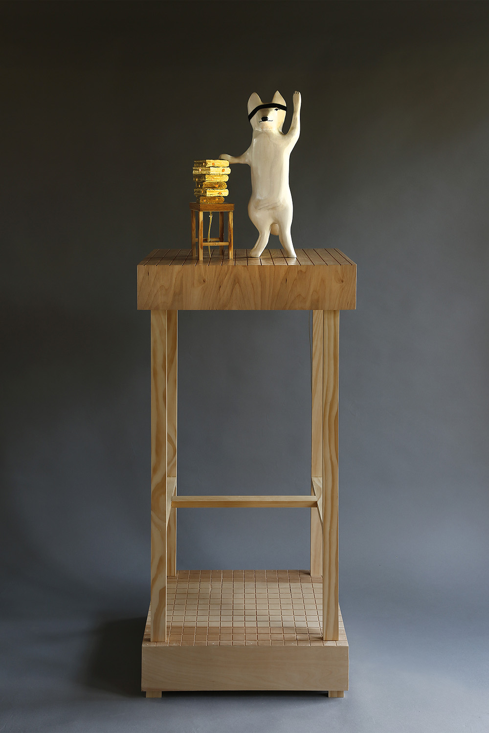 """Fox Swearing on a Stack of Holey Books"", 62"" h x 21"" w x 18"" d; wood, stain, plexiglass, gold leaf, felt, LED light; © Tom Gormally 2019"