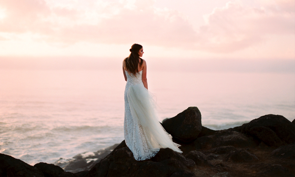The play of the light, the gorgeous pink tone in the sky, and the stunning contrast of the delicate tulle against the rough rock makes for an unbeatable composition.