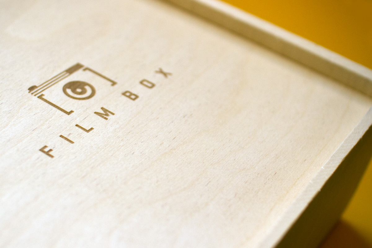 Detail of custom logo laser engraving etched into wood box direct mail kit.