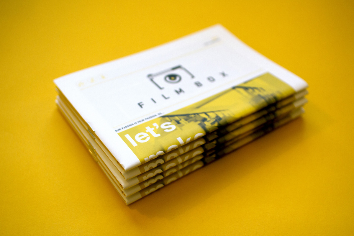 Stack of mini newspapers custom printed and designed for Film Box marketing materials and collateral.