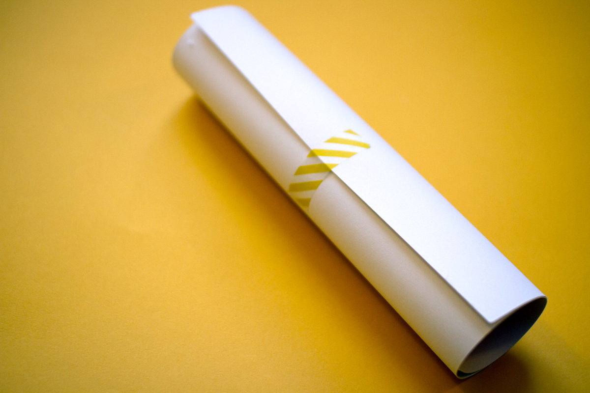 Screen printed poster is rolled up and held together with white and yellow striped washi tape.