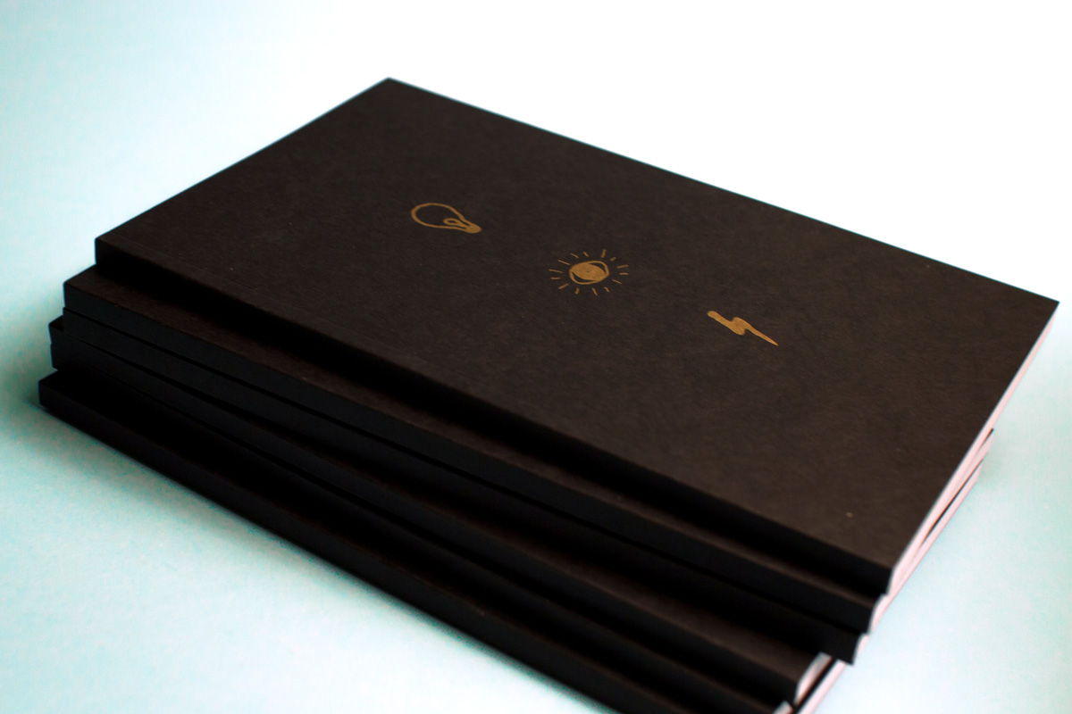 Stack of black cover and gold metallic ink printed the illumination project journals.