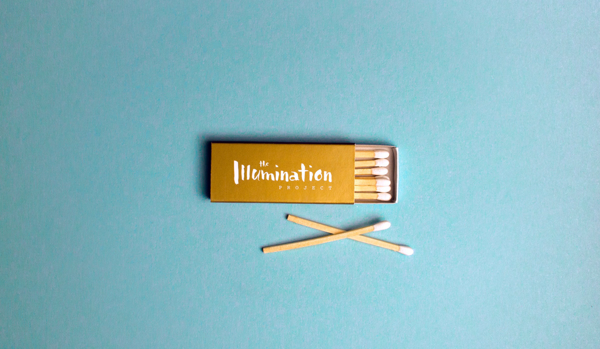 Custom designed matchboxes with white tip matches and the Illumination Project logo in white on a metallic gold pantone box.