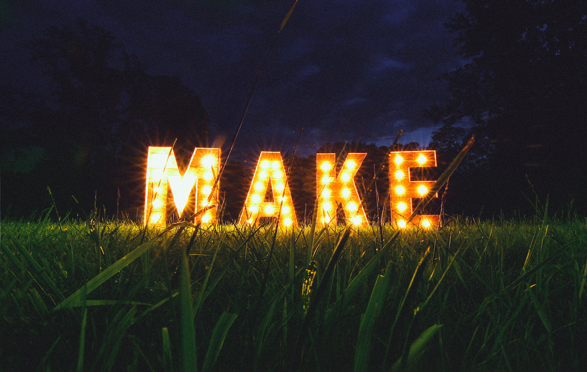 Wooden box letters with lightbulbs in them illuminate the word MAKE in a grass field.