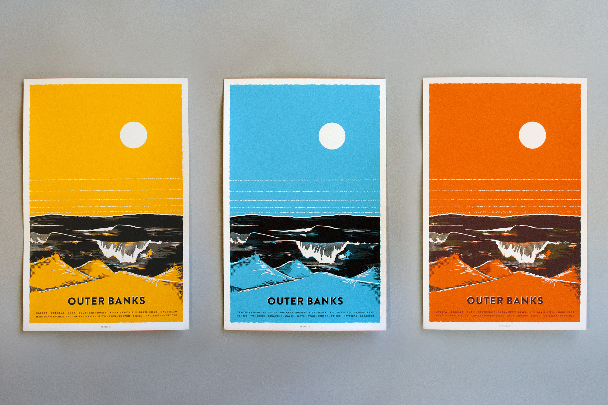 All three illustrated OBX poster prints for Bearings guide in gold, blue, and orange colorway options show a surfer and the dunes of the Outer banks under a large horizon and sun.
