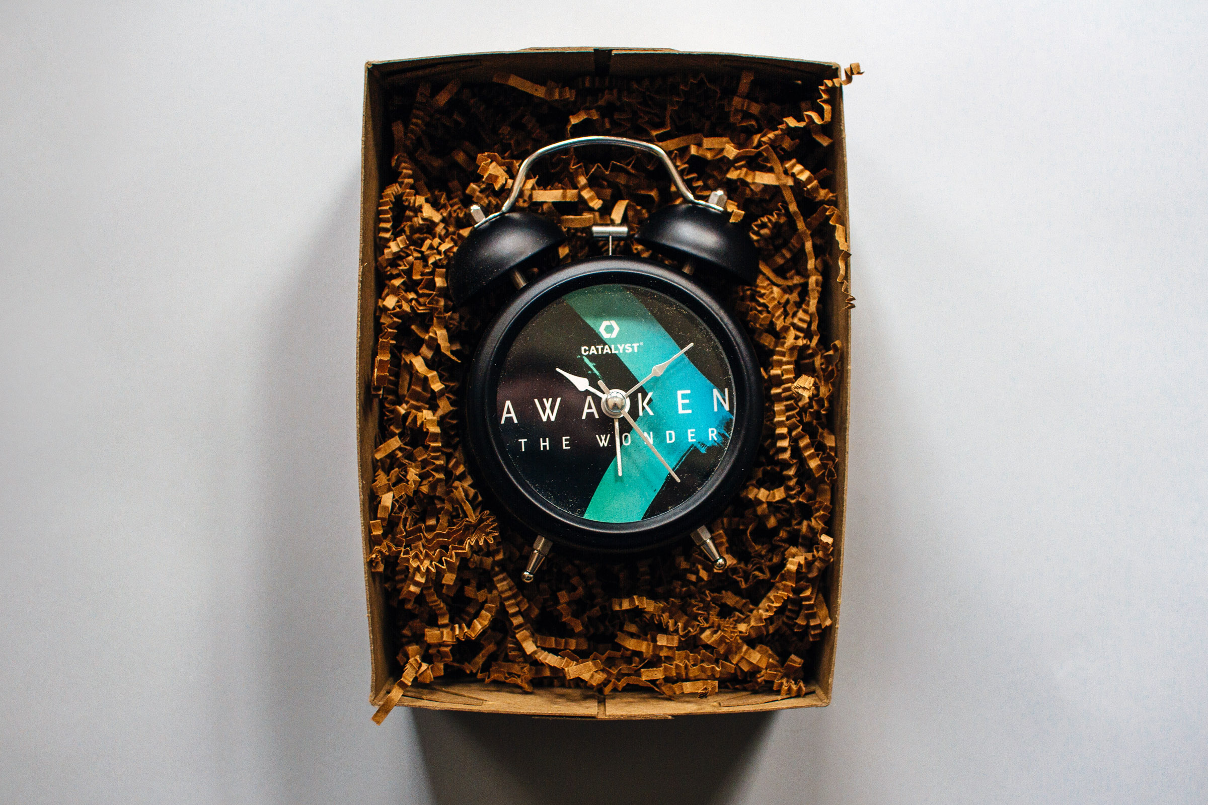 Custom printed vintage alarm clock for Catalyst Conference 2015 Atlanta Awaken the Wonder event theme promotion in a box surrounded by kraft krinkle paper