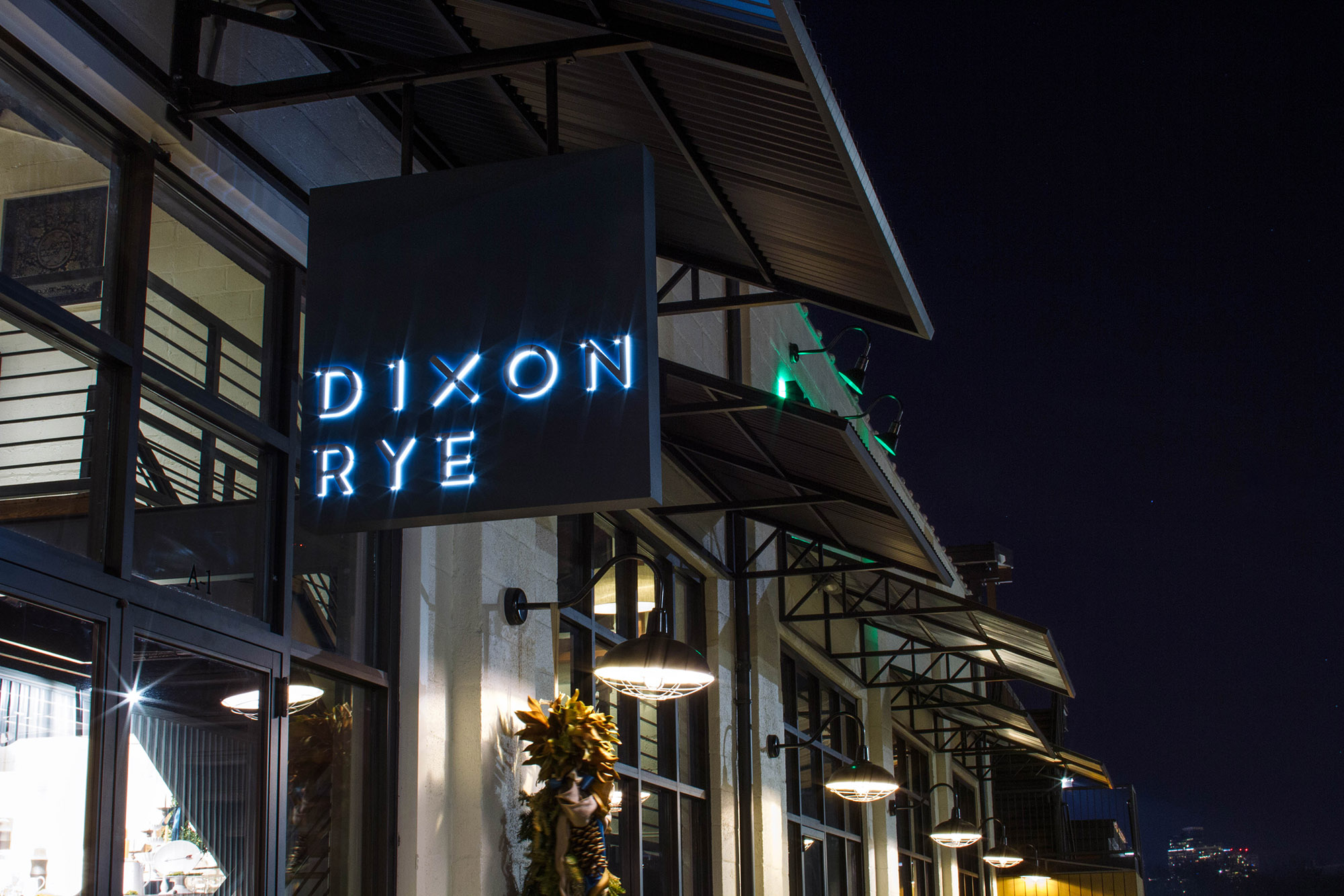 Exterior of Dixon Rye's retail store showing the raised letters of the logo design with white light illuminating the sign behind them, and the night skyline of Atlanta in the background.