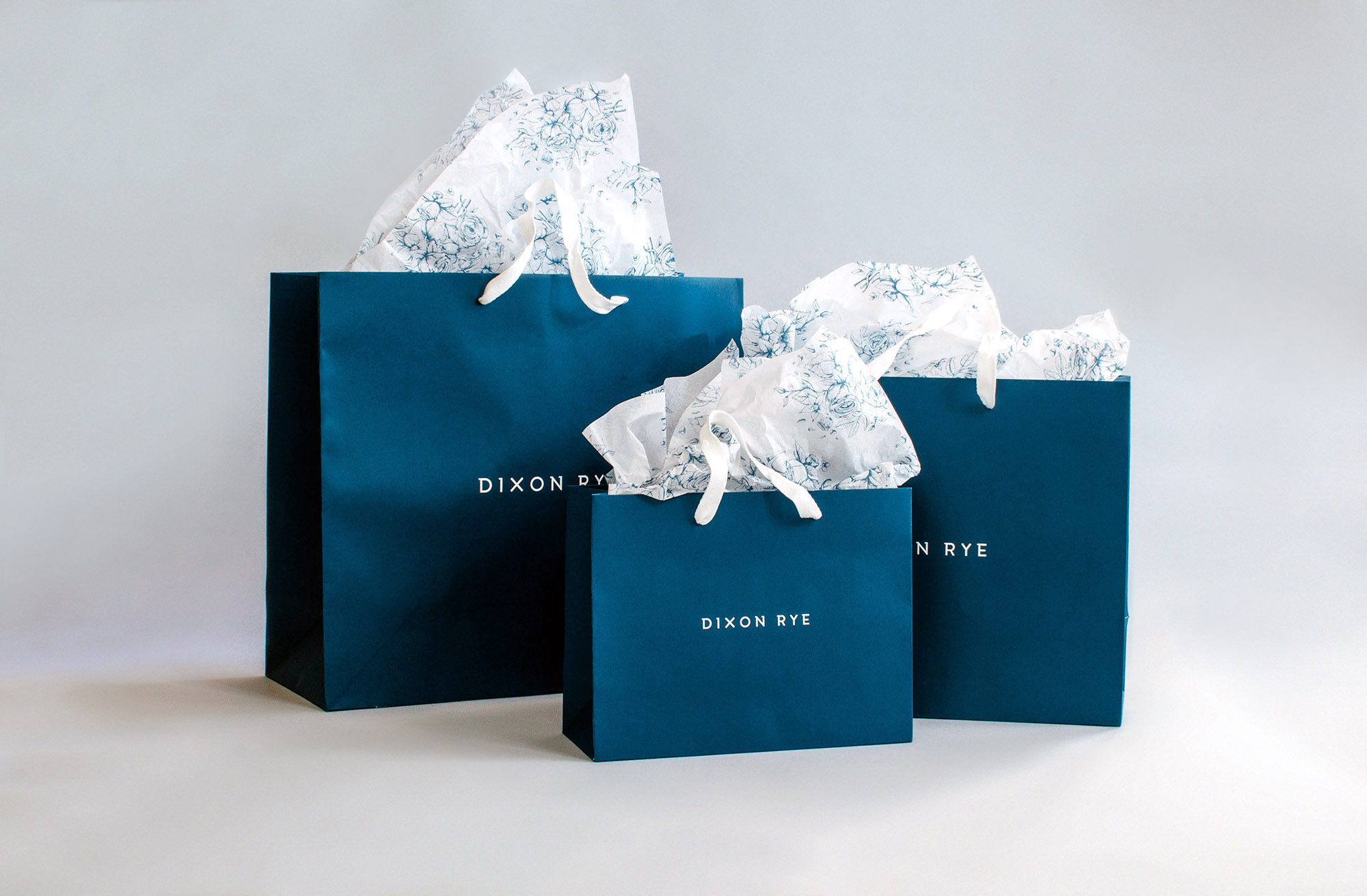 Navy retail packaging design and hand illustrated floral pattern on white tissue paper, set of three sizes, all in a row.