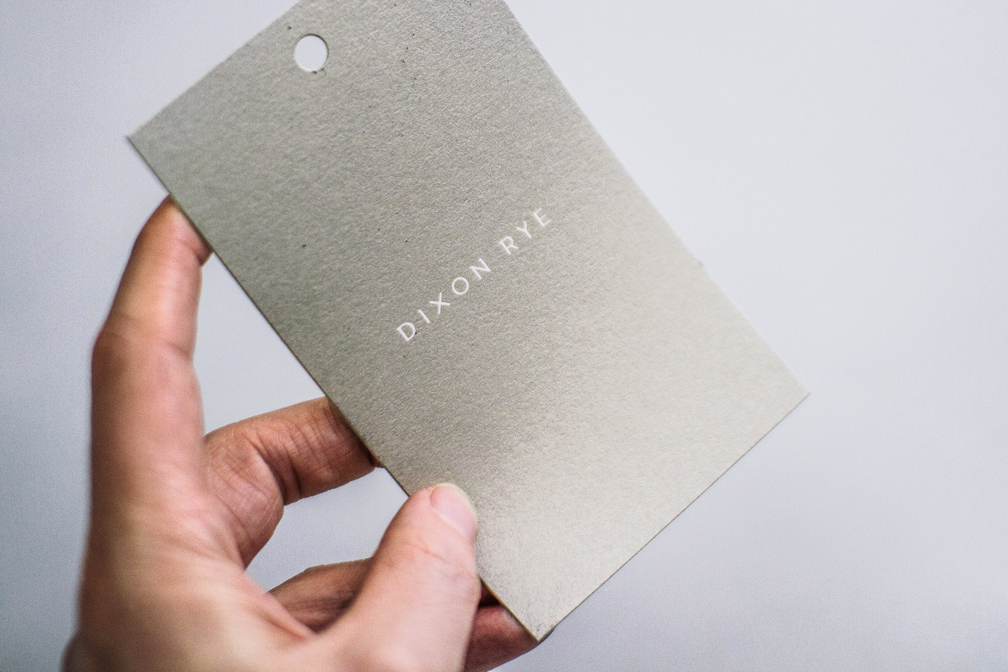 White logo on metallic silver screen printed custom hang tag for Dixon Rye Atlanta store sign and product tag, one large rectangle tag detail