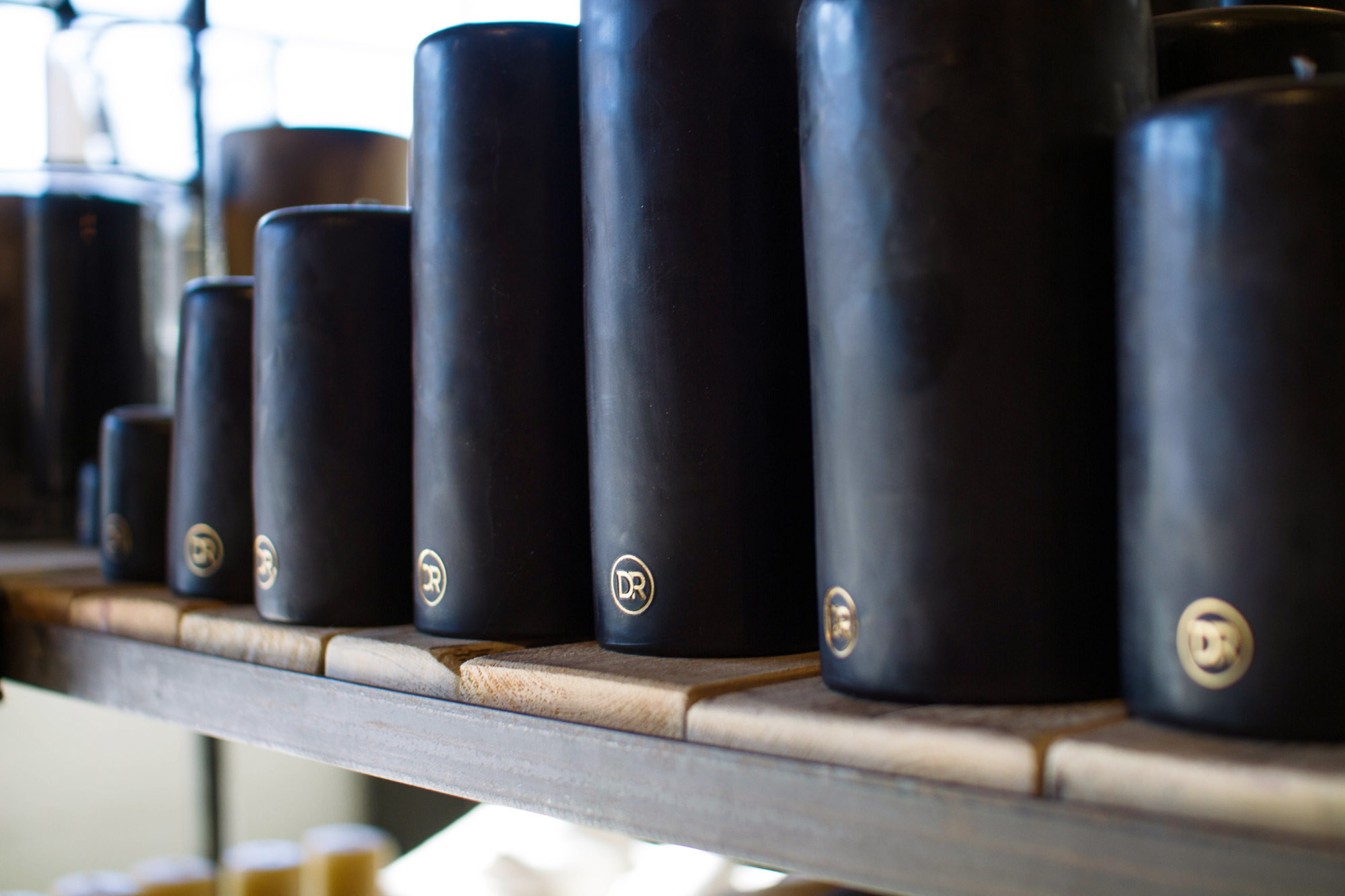 Black pillar candles with custom Dixon Rye DR circle icon stamped into the wax in gold on the side