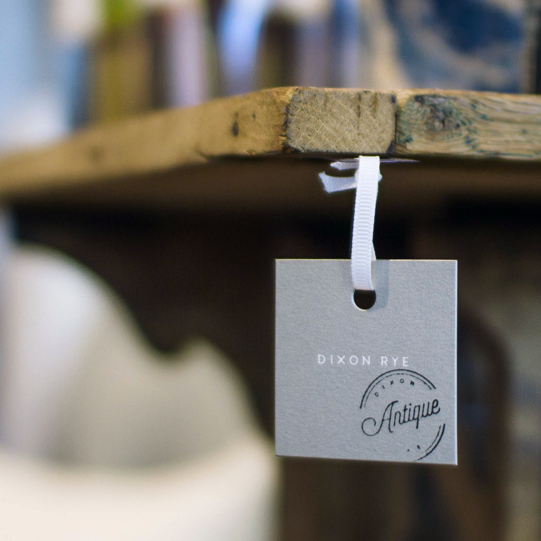 Dixon Rye retail product tag white logo on metallic silver small square with Antique script lettering circle stamp